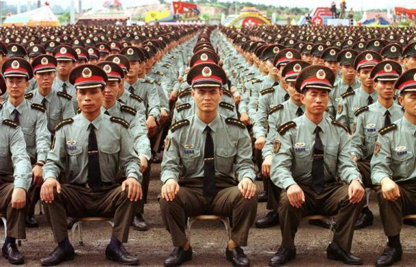 Chinese People's Liberation Army (PLA) troops sit in rows as they listen to speeches in the south China economic boom town of Shenzhen, June 30, 1997, during a farewell ceremony before crossing the border into Hong Kong July 1.