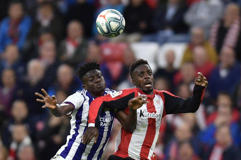 Athletic Bilbao's Inaki Williams, right, jumps for the ball in front Valladolid's Mohammed Salisu before scoring his goal during the Spanish La Liga soccer match between Athletic Bilbao and Valladolid at San Mames stadium in Bilbao, northern Spain, Sunday, Oct. 20, 2019. (AP Photo/Alvaro Barrientos)