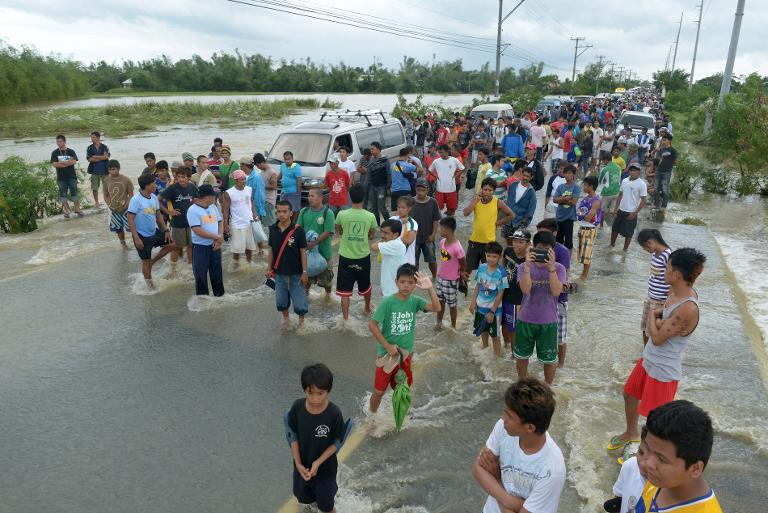 Stranded people stand as vehicles maneuver though flood waters after Typhoon Nari swept across the northern Philippines, on October 12, 2013