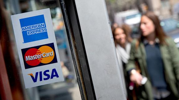 Window sticker showing logos for credit card issuers | Bloomberg/Getty Images