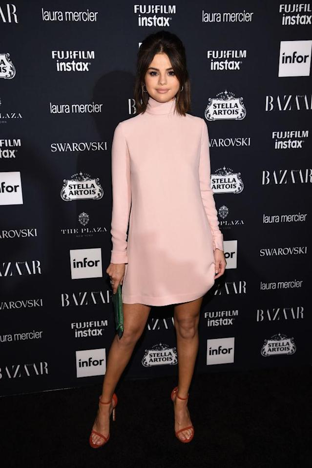 "<p>The singer rocked a baby pink, long-sleeve mini <a href=""https://www.instagram.com/p/BYzVigPlozc/?taken-by=checkthetag"" rel=""nofollow noopener"" target=""_blank"" data-ylk=""slk:Valentino dress"" class=""link rapid-noclick-resp"">Valentino dress</a> to the Harper's Bazaar Icons event that evening, pairing her look with a green bag and red strappy heels. (Photo: Getty Images) </p>"