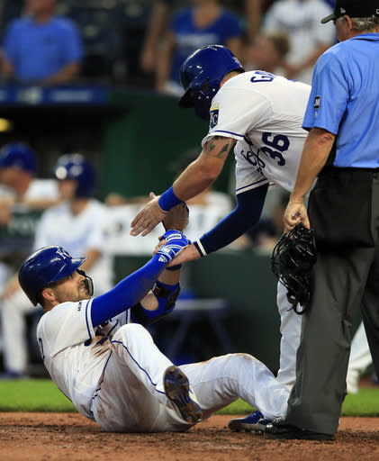 Kansas City Royals Whit Merrifield, left, is helped up by teammate Cam Gallagher (36) after his inside-the-park home run during the fourth inning of a baseball game against the Chicago White Sox at Kauffman Stadium in Kansas City, Mo., Tuesday, July 16, 2019. (AP Photo/Orlin Wagner)