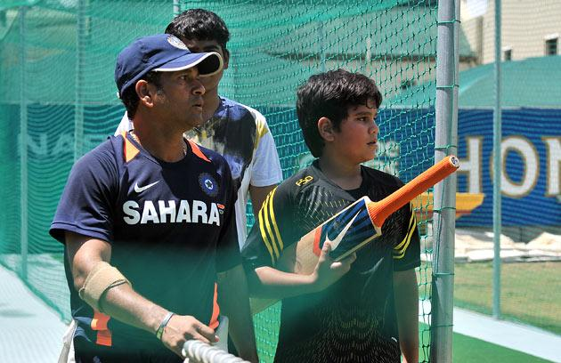 Indian superstar cricketer Sachin Tendulkar (L) talks with his son Arjun during a training at Newlands Stadium in Cape Town on Janurary 1, 2011 on the eve of the third test between South Africa and India.  AFP PHOTO / ALEXANDER JOE
