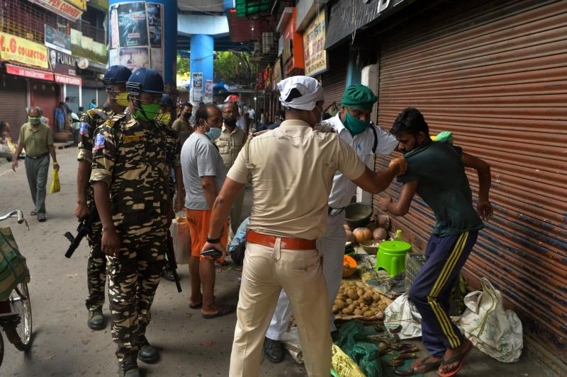 Police personnel orders sellers to clear a roadside market area during a lockdown imposed until July 29 as a preventive measure against the spread of the COVID-19 coronavirus in Siliguri on July 26, 2020. (Photo by Diptendu DUTTA / AFP) (Photo by DIPTENDU DUTTA/AFP via Getty Images)
