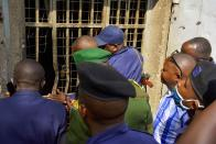 Congolese security officers look at a broken window at the Kangbayi central prison in Beni