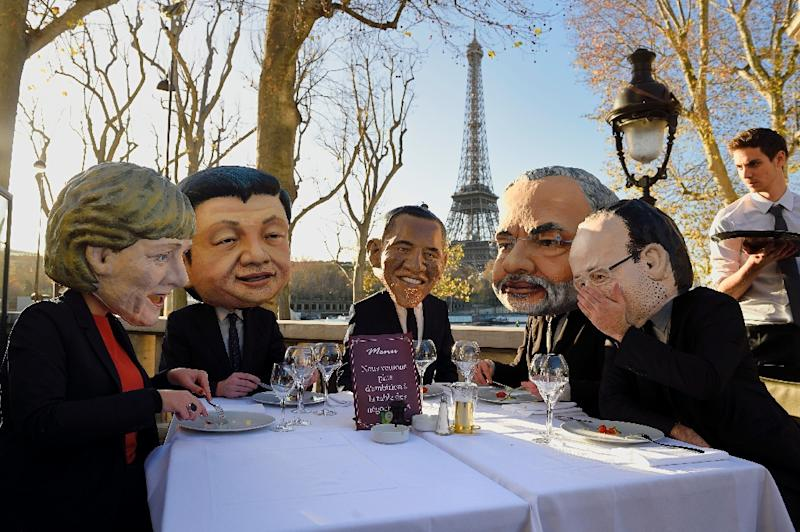 Performers wearing effigies of world leaders gather for a breakfast organized by Oxfam on November 28, 2015 in Paris (AFP Photo/Eric Feferberg)