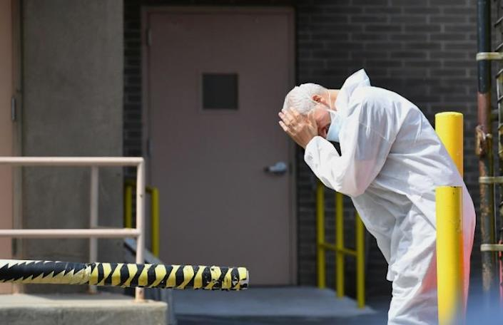 A medical personnel rubs his face outside the Wyckoff Heights Medical Center in Brooklyn, New York (AFP Photo/Angela Weiss)