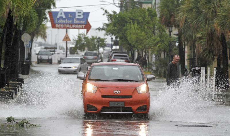 A car goes through a flooded street due to heavy rains in Key West, Fla., Sunday, Aug. 26, 2012 as heavy winds and rain hit the northern coast. Rain bands from Tropical Storm Isaac are expected to continue streaming across Marion County Monday as the ninth named storm of the 2012 hurricane season continues toward the northern Gulf of Mexico. National Weather Service officials in Jacksonville on Sunday said Marion County began getting rain bands from Isaac around 2 p.m. and that the rain would continue through Tuesday. (AP Photo/Alan Diaz)
