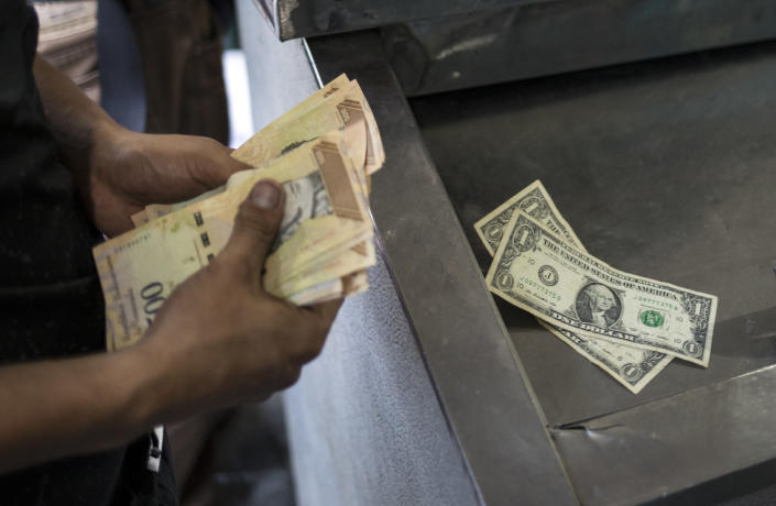 A man counts his Bolivars and Dollars to pay for items at a market in Caracas, Venezuela, Sunday, May 19, 2019. On May 13, Venezuela lifted foreign exchange controls on banks for the first time in 16 years. (AP Photo/Rodrigo Abd)