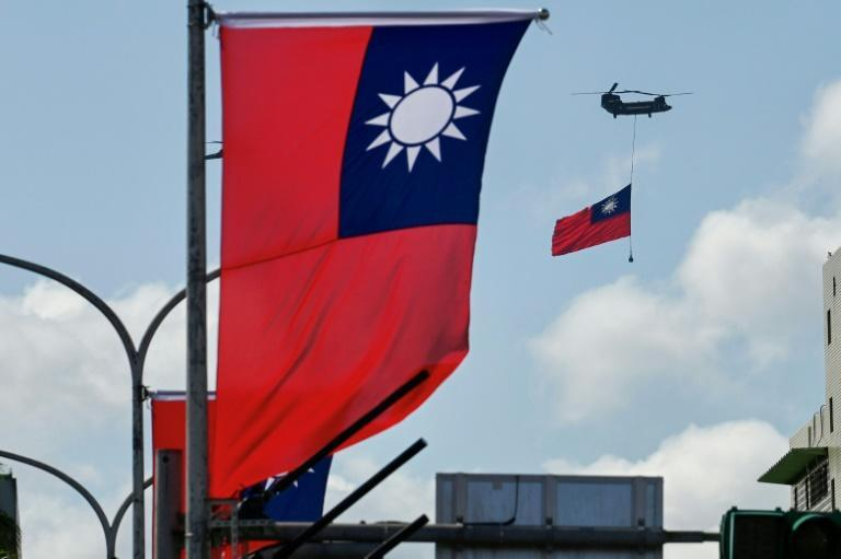 A CH-47 Chinook helicopter carries a Taiwan flag during national day celebrations in Taipei on October 10, 2021 (AFP/Sam Yeh)