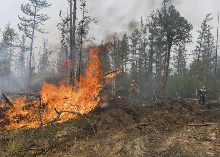 FILE - In this Sunday, July 18, 2021 file photo, volunteers and employees of the Yakutlesresurs extinguish a forest fire outside Magaras village 87 km. (61 miles) west of Yakustk, the capital of the republic of Sakha also known as Yakutia, Russia Far East. Each year, thousands of wildfires engulf wide swathes of Russia, destroying forests and shrouding broad territories in acrid smoke. This summer has seen particularly massive fires in Yakutia in northeastern Siberia following unprecedented heat. (AP Photo/Alexey Vasilyev, File)