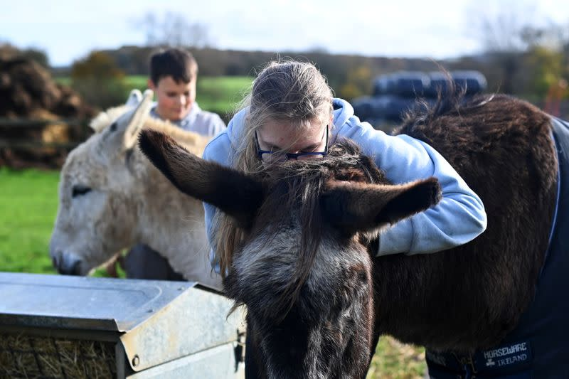 Emily Trice relaxes as she connects with her favourite donkey Milly, during a visit to Future Roots in Sherborne