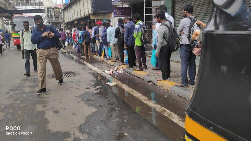 People gather at a bus stop at Bandra West.