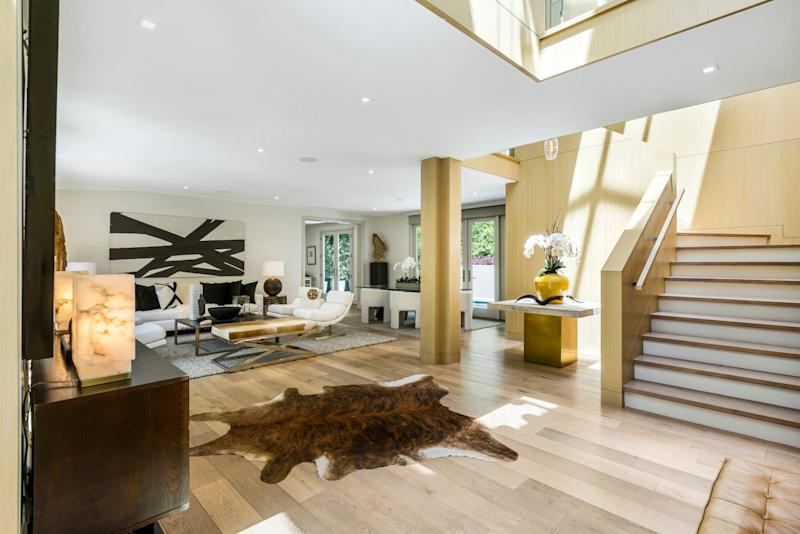 The contemporary-style house features gallery walls, a vaulted entry and two primary bedrooms.
