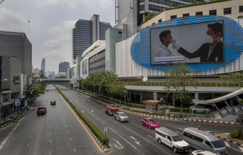 An educational visual on the prevention of the new coronavirus prevention is shown on a giant screen in a nearly-deserted intersection in Bangkok, Thailand, Thursday, April 2, 2020.  A state of emergency has been declared in the country to allow the government to impose stricter measures to control the coronavirus that has infected hundreds of people in the region. The new coronavirus causes mild or moderate symptoms for most people, but for some, especially older adults and people with existing health problems, it can cause more severe illness or death. (AP Photo/Gemunu Amarasinghe)