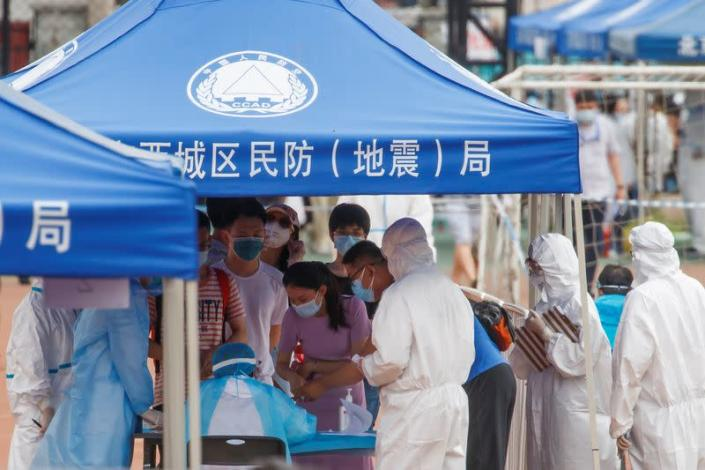 People line up to get tested at the Guangan Sport Center after an unexpected spike of cases of the coronavirus disease (COVID-19) in Beijing