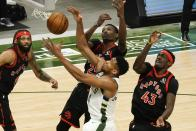 Milwaukee Bucks' Giannis Antetokounmpo and Toronto Raptors' Chris Boucher go after a rebound during the first half of an NBA basketball game Tuesday, Feb. 16, 2021, in Milwaukee. (AP Photo/Morry Gash)