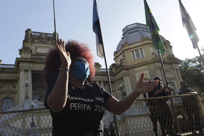 """A woman protests against crimes committed by the police against black people in the favelas, outside the Rio de Janeiro's state government, Brazil, Sunday, May 31, 2020. The protest, called """"Black lives matter,"""" was interrupted when police used tear gas to disperse people. """"I can't breathe"""", said some of the demonstrators, alluding to the George Floyd's death. (AP Photo/Silvia Izquierdo)"""