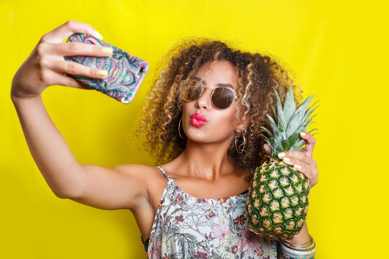 A young woman takes a selfie with a pineapple.