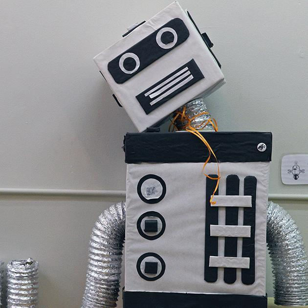 A watchful robot sitting in a corner of the workshop, looking over the young robot makers.