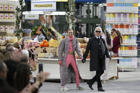 """German designer Karl Lagerfeld (R) and model Cara Delevingne appear at the end of his Fall/Winter 2014-2015 women's ready-to-wear collection show for French fashion house Chanel at the Grand Palais transformed into a """"Chanel Shopping Center"""" during Paris Fashion Week March 4, 2014. REUTERS/Stephane Mahe"""