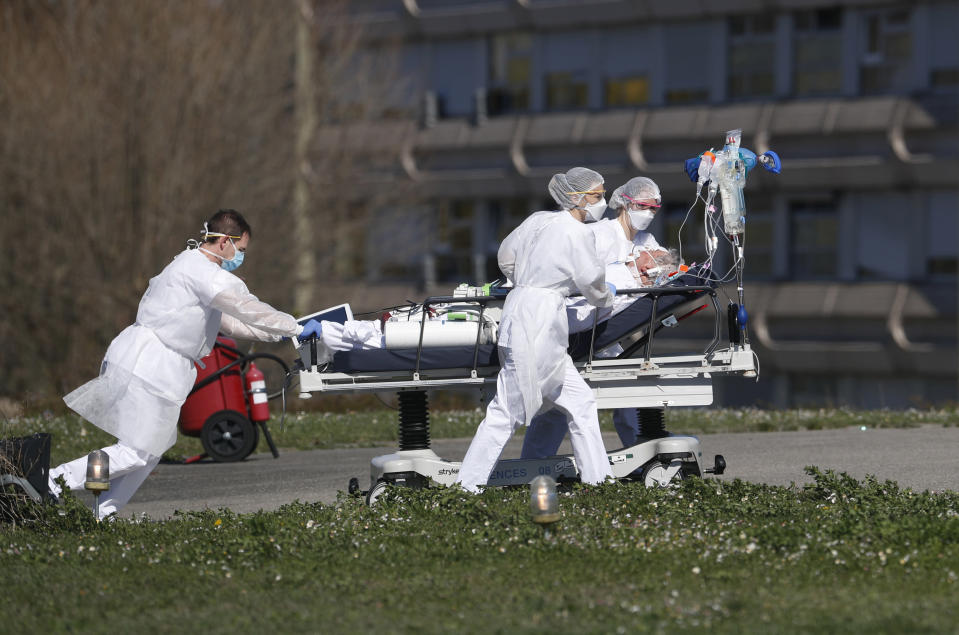 FILE - In this March 23, 2020 file photo, a victim of the COVID-19 virus is evacuated from the Mulhouse civil hospital, eastern France. The picture is still grim in parts of Europe and Asia as variants of the virus fuel an increase in new cases and the worldwide death toll closes in on 3 million. (AP Photo/Jean-Francois Badias, File)