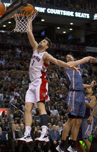 Toronto Raptors forward Andrea Bargnani dunks past Charlotte Bobcats center Byron Mullens (22) during the first half of an NBA basketball game in Toronto on Tuesday, April 3, 2012. (AP Photo/The Canadian Press, Frank Gunn)