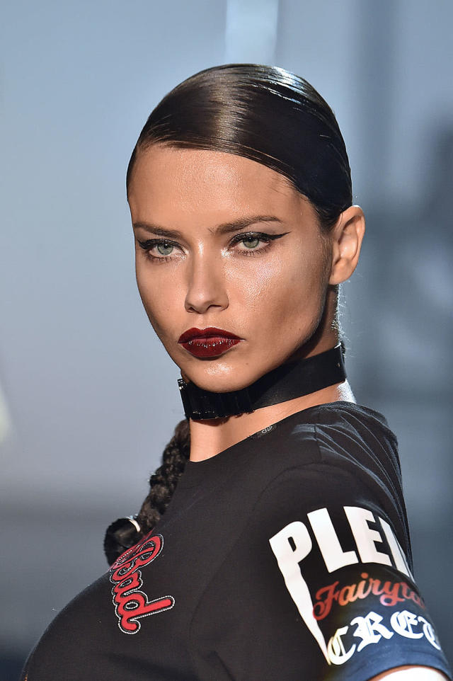<p>Paired with a graphic cat eye, this glossy dark red lip creates a vampy effect on Adriana Lima. On this runway, makeup looks were individualized, and no two were exactly the same.(Photo: Getty Images) </p>