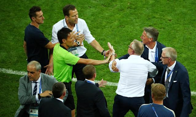 Sweden manager Janne Andersson, fourth from right, and Germany's Oliver Bierhoff, fifth from left, clash at the end of the match in Sochi.