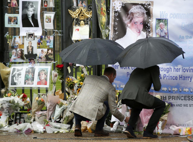 <p>Britain's Prince William, left, and Prince Harry place flowers and tributes taken from members of the public at the Golden Gates of Kensington Palace, London, Aug. 30, 2017 on the eve of the 20th anniversary of their mother's death. (Photo: Alastair Grant/AP) </p>