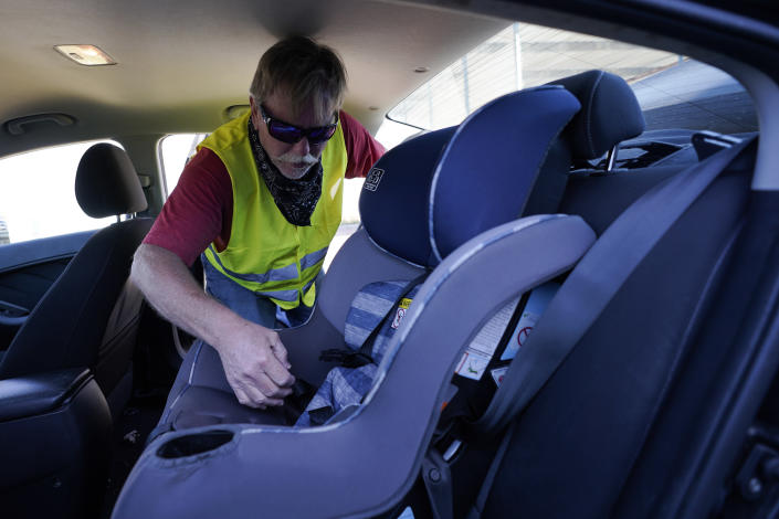 Dave, who declined to give his last name, from Toledo, Ohio, installs a child seat in his vehicle as he waits to for his friend Ruth, a Haitian migrant, her husband and their 3-year-old daughter, who he believes continue to be in U.S. Customs and Border Protection custody, Friday, Sept. 24, 2021, in Del Rio, Texas. Dave, who has been to Haiti many times and befriended Ruth on one of his trips, drove down from Ohio to Southwest Texas in hopes of picking the family up and driving them to Ohio, where Ruth has family awaiting them. (AP Photo/Julio Cortez)