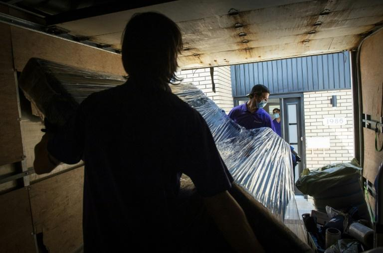 Movers carry Sheila Dassin's belongings into her new abode on July 1 in the Montreal suburb of Laval