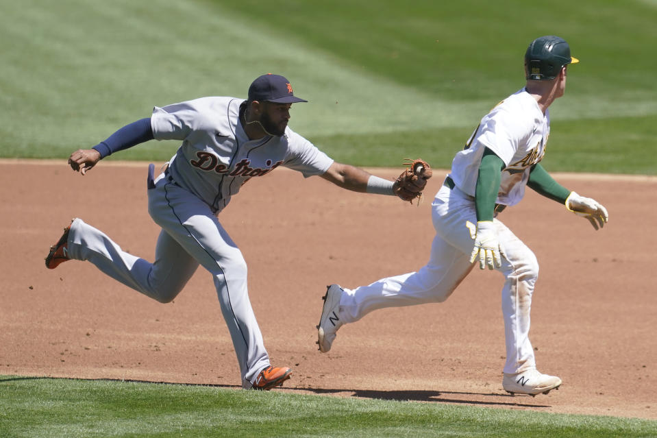 Oakland Athletics Mark Canha, right, is caught in a rundown before being tagged out by Detroit Tigers shortstop Willi Castro, left, during the first inning of a baseball game in Oakland, Calif., Sunday, April 18, 2021. (AP Photo/Jeff Chiu)