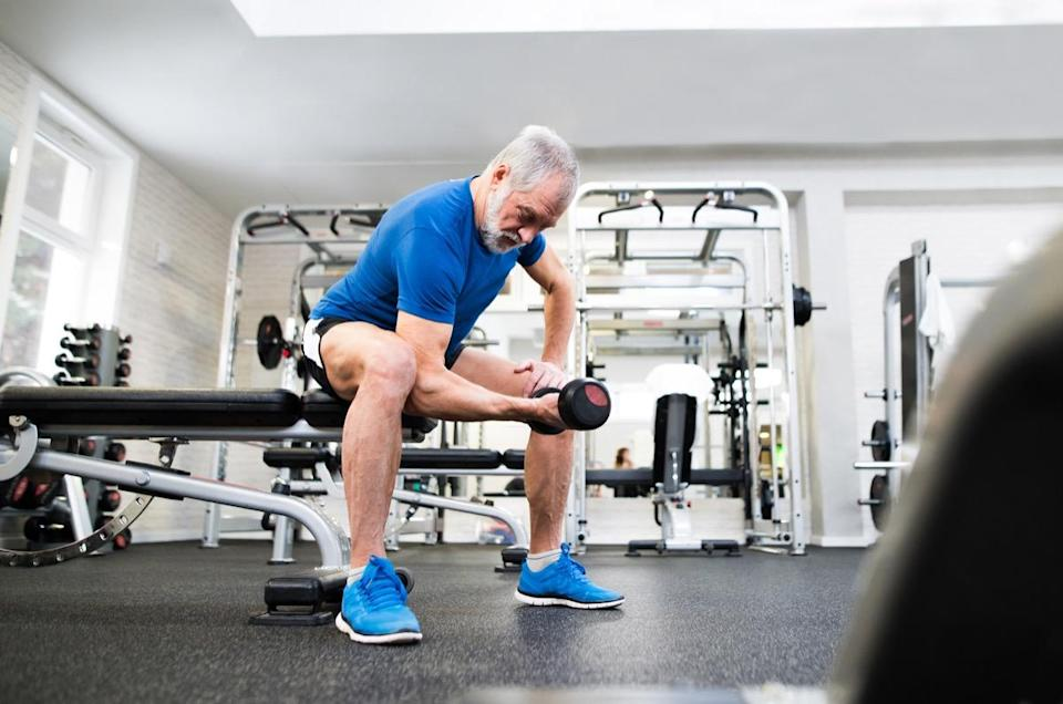 Senior man in sports clothing in gym working out with weights