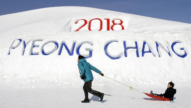 In this Feb. 19, 2011 file photo, a South Korean father pulls his son on a sled in front of a sign promoting the Pyeongchang 2018 Winter Olympics in Pyeongchang, east of Seoul, South Korea. The people of Pyeongchang can confidently promise two things when they host the Olympics: it'll be cold, and there'll be no concerns about snow. While a warm spell has created challenging conditions for the skiers and snowboarders competing in the mountains above Sochi at the 2014 edition, there's been heavy dumps of snow in the region that will host the next Winter Games in 2018