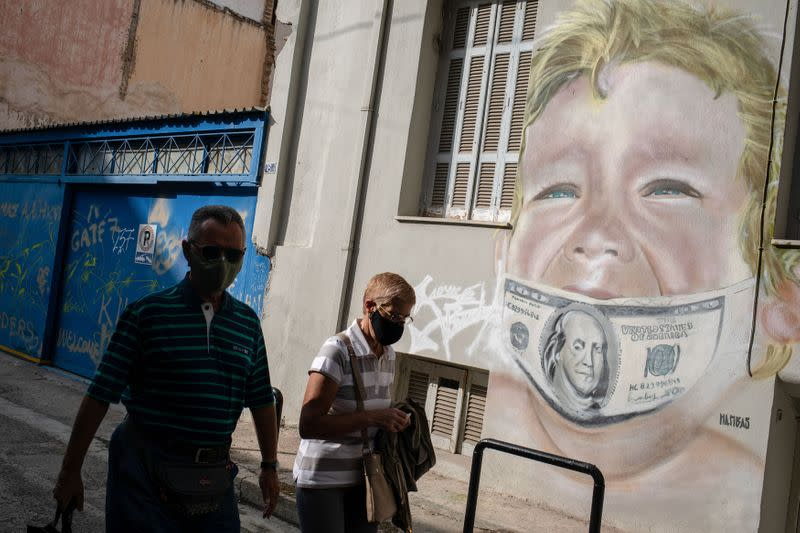 People wearing protective face masks walk past a mural by Greek visual artist Hambas, amid the coronavirus disease (COVID-19) pandemic, in Athens