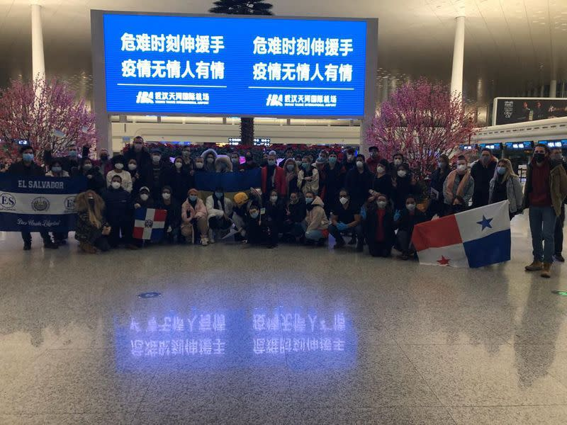 Tourists from around the world pose for a photograph at the airport in Wuhan