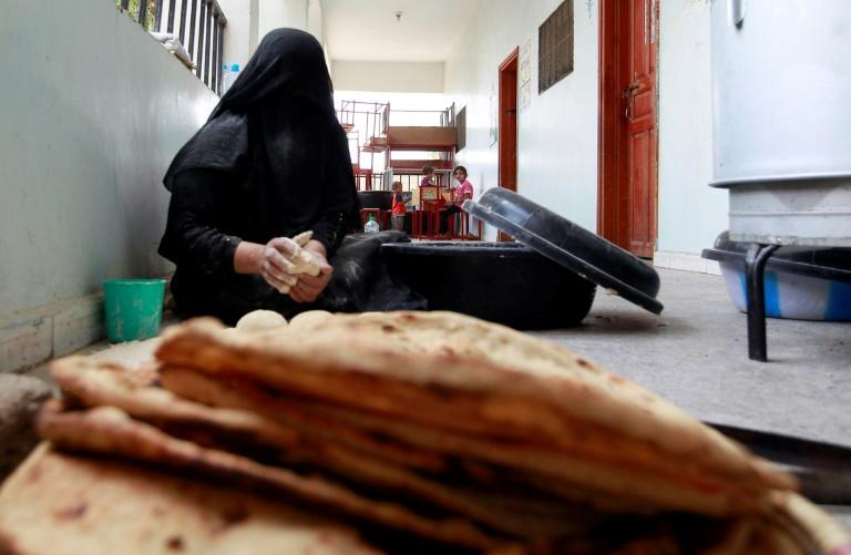A displaced Yemeni woman makes bread at a school turned into a shelter in 2015 in the capital Sanaa