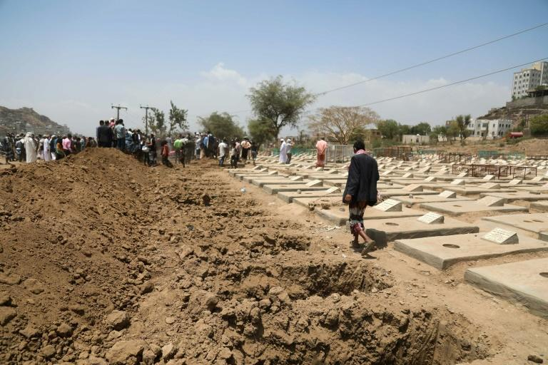 Yemenis gather close to graves for cornavirus victims at a cemetery in the Yemeni city of Taez