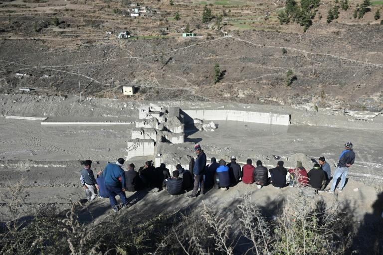 People look at the remains of a dam in Tapovan in the Indian Himalayas that was swept away by a flash flood believed caused by a massive chuck of glacier breaking off high in the mountains