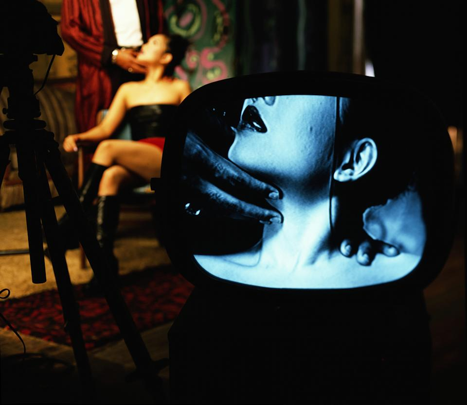 Young woman sitting on chair, man holding face, video screen in fore
