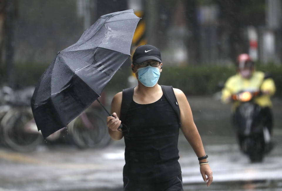 A man struggles with his umbrella against powerful gusts of wind generated by Typhoon Chanthu in Taipei, Taiwan, Sunday, Sept. 12, 2021. Typhoon Chanthu drenched Taiwan with heavy rain Sunday as the storm's center passed the island's east coast heading for Shanghai. (AP Photo/Chiang Ying-ying)