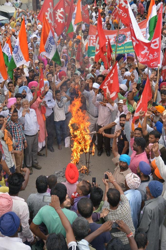 Leftist activists shout slogans as they burn an effigy of Indian Prime Minister Narendra Modi during a nationwide strike against the central government in Amritsar, northwest India on September 2, 2015 (AFP Photo/Narinder Nanu)
