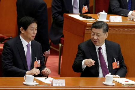 Chinese President Xi Jinping (R) talks to Chinese Politburo Standing Committee member Li Zhanshua, as delegates vote at the fifth plenary session of the National People's Congress (NPC) at the Great Hall of the People in Beijing, China March 17, 2018.  REUTERS/Jason Lee