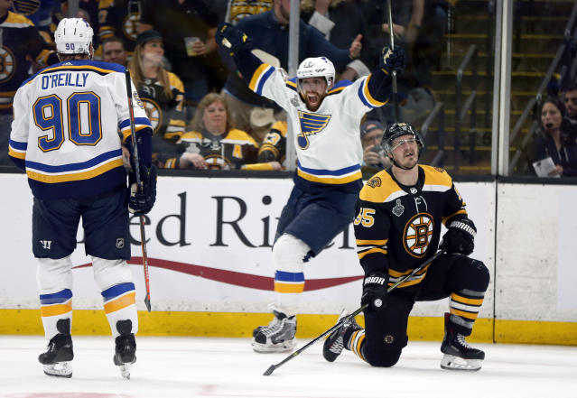 St. Louis Blues' David Perron, center, celebrates his goal behind Boston Bruins' Noel Acciari, right, during the third period in Game 5 of the NHL hockey Stanley Cup Final, Thursday, June 6, 2019, in Boston. (AP Photo/Michael Dwyer)