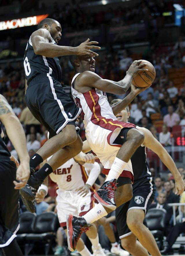 Brooklyn Nets shooting guard Alan Anderson (6) fouls Miami Heat point guard Norris Cole (30) as Cole goes to the basket in the first period of an NBA preseason basketball game, Friday, Oct. 25, 2013, in Miami. (AP Photo/Alan Diaz)