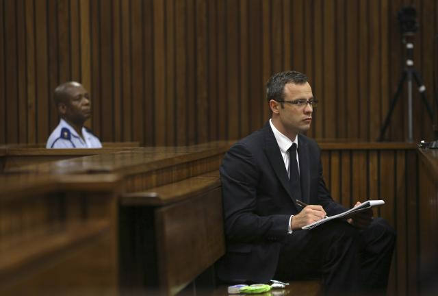 Olympic and Paralympic track star Oscar Pistorius takes notes during court proceedings at the North Gauteng High Court in Pretoria March 13, 2014. Pistorius is on trial for murdering his girlfriend Reeva Steenkamp at his suburban Pretoria home on Valentine's Day last year. REUTERS/Themba Hadebe/Pool (SOUTH AFRICA - Tags: SPORT CRIME LAW ATHLETICS)