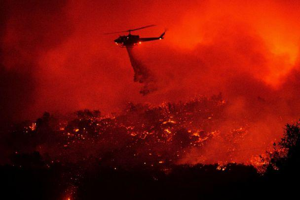 PHOTO: A helicopter drops water on the Cave Fire burning along Highway 154 in Los Padres National Forest, Calif., above Santa Barbara, Nov. 26, 2019. (Noah Berger/AP)