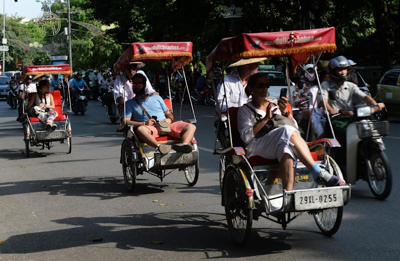 Tourists tour downtown Hanoi on July 16, 2014 (AFP Photo/Hoang Dinh Nam)