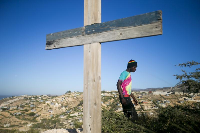 A resident walks past a cross during a memorial service honoring the victims of the 2010 earthquake, at Titanyen, a mass burial site north of Port-au-Prince, Haiti, Sunday, Jan. 12, 2020. Sunday marks the 10th anniversary of the devastating 7.0 magnitude earthquake that destroyed an estimated 100,000 homes across the capital and southern Haiti, including some of the country's most iconic structures. (AP Photo/Dieu Nalio Chery)